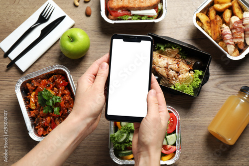Fototapeta Top view of woman holding smartphone over wooden table with lunchboxes,  mockup for design. Healthy food delivery obraz
