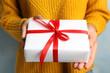 Leinwandbild Motiv Young woman holding Christmas gift on blue background, closeup
