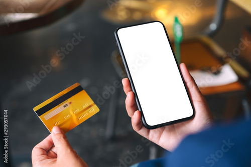 Fototapeta Mockup image of a hands holding credit card and a black mobile phone with blank desktop screen obraz