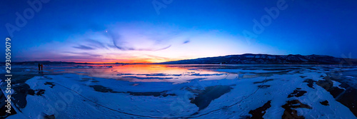 colorful sunset on winter crack ice lake Baikal . Wide panorama Canvas Print