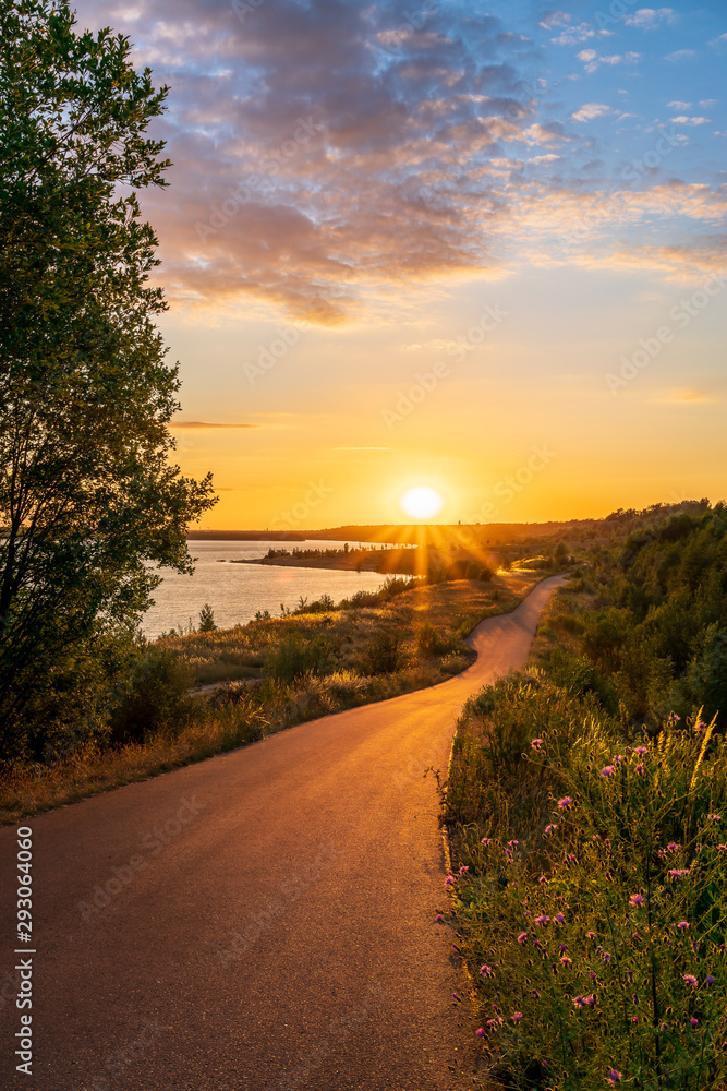 Fototapeta Asphalt road along a lake during a beautiful summer sunset