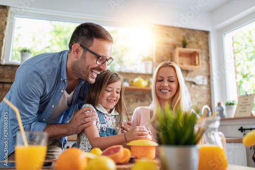 Foto Happy family makes orange juice for breakfast