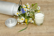 Glass Milk And Wild Flowers In The Milk Churn On Wooden Table