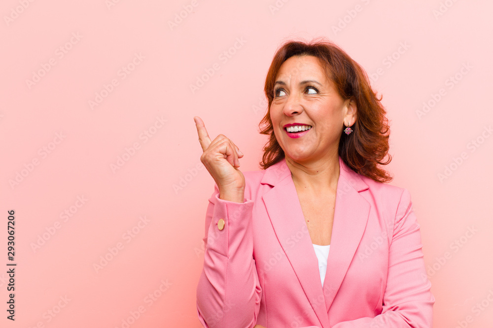 Fototapeta middle age woman smiling happily and looking sideways, wondering, thinking or having an idea against pink wall