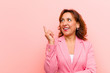 canvas print picture middle age woman smiling happily and looking sideways, wondering, thinking or having an idea against pink wall