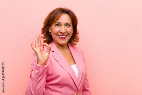 Photo middle age woman feeling happy, relaxed and satisfied, showing approval with oka
