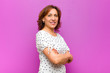 canvas print picture middle age woman smiling to camera with crossed arms and a happy, confident, satisfied expression, lateral view against purple wall