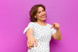 canvas print picture - middle age woman feeling happy and confident, pointing to camera with both hands and laughing, choosing you against purple wall