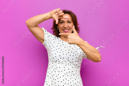 canvas print motiv - kues1 : middle age woman feeling happy, friendly and positive, smiling and making a portrait or photo frame with hands against purple wall