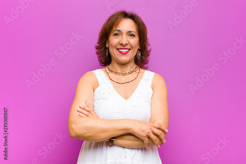 canvas print motiv - kues1 : middle age woman looking excited and surprised, open-mouthed with both hands on head, feeling like a lucky winner against purple wall