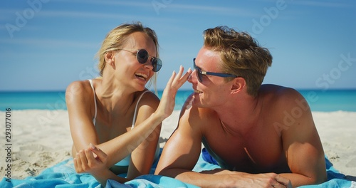 Photo A happy young couple is having fun to apply a sunscreen or sun tanning lotion to take care of their skin during a vacation on a beach