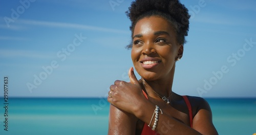 Photo A happy young african woman is applying a sunscreen or sun tanning lotion to take care of her skin during a vacation on a beach