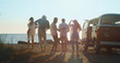 canvas print picture - A group of young multi-ethnic friends just arrived with a minivan are having fun to start a vacation a beach with a sea on a sunset.