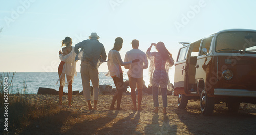 A group of young multi-ethnic friends just arrived with a minivan are having fun to start a vacation a beach with a sea on a sunset Wallpaper Mural