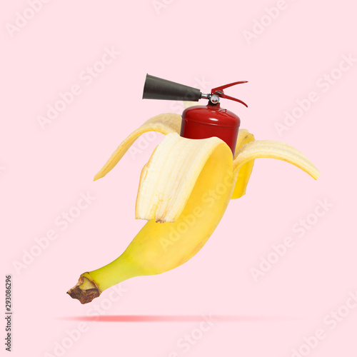 Obraz Unusual combination of usual things. Fire extinguisher as a banana on trendy coral background. Negative space. Modern design. Copyspace. Contemporary art. Creative conceptual and colorful collage. - fototapety do salonu