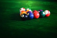 Man's Hand And Cue Arm Playing Snooker Game Or Preparing Aiming To Shoot Pool Balls On A Green Billiard Table. Colorful Snooker Balls On Green Frieze.