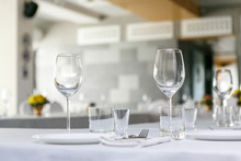 A Front View Of Wine Glasses And Dishes In The Restaurant Table Set