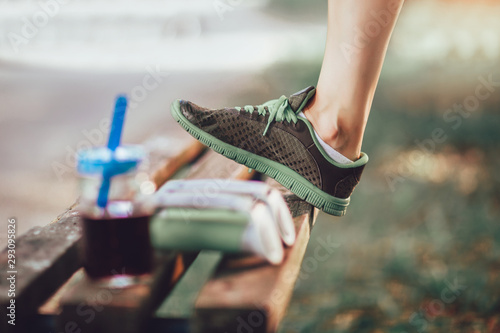 Woman raised her leg on the bench, after training in nature - 293095826
