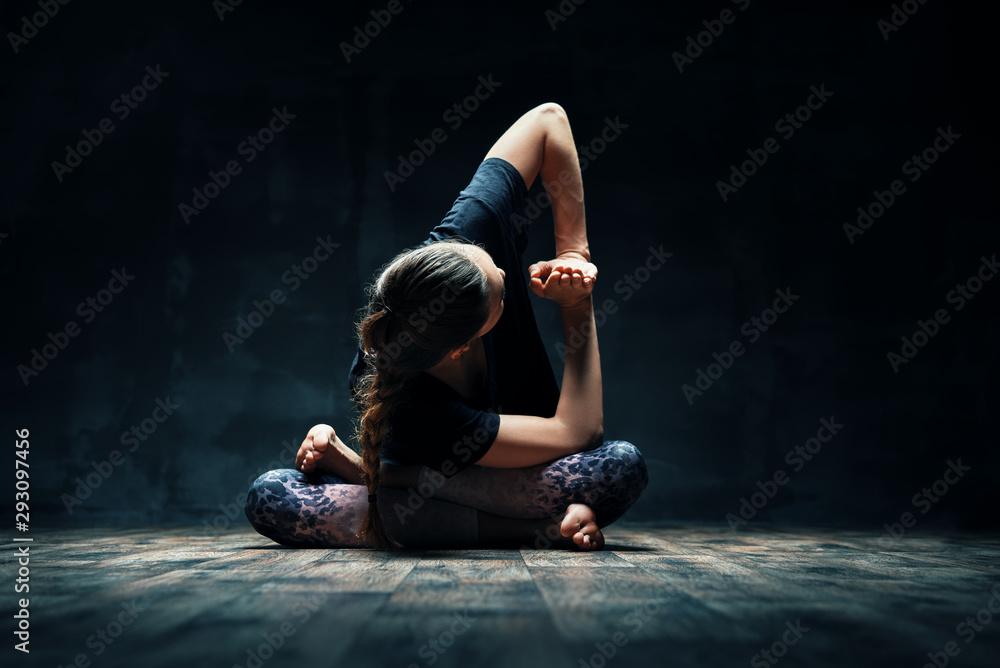 Fototapeta Young woman doing yoga Padmasana pose variation on dark room