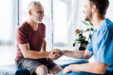 selective focus of happy patient shaking hands with doctor