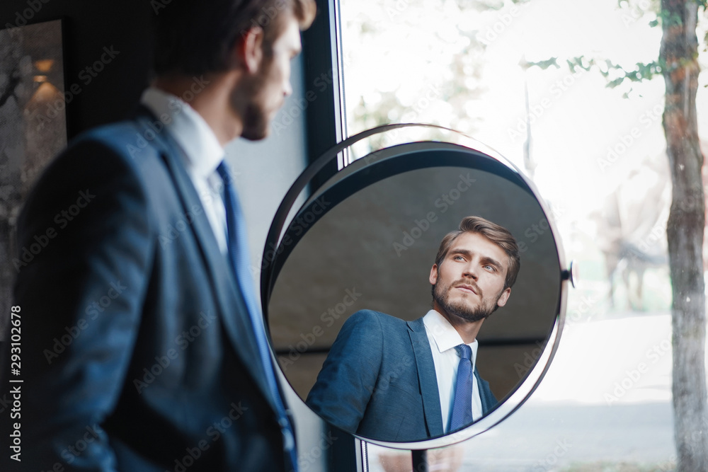 Fototapeta Reflection of handsome young man in full suit standing near the window in front of the mirror indoors
