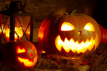 Two Halloween Pumpkins With Gl...