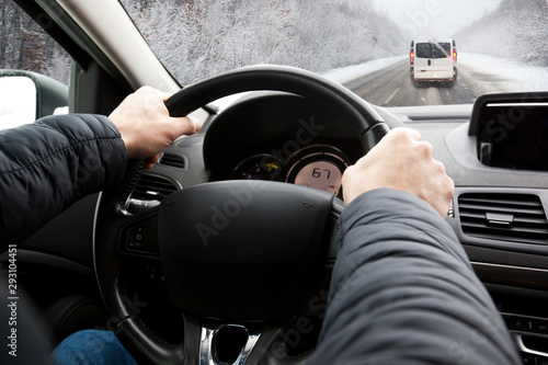 fototapeta na ścianę The young man is driving on his car through sne snowy road