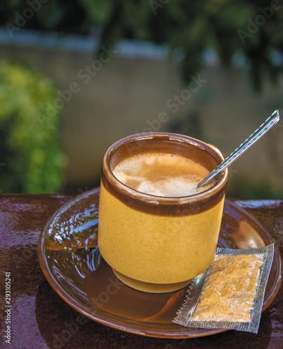 Café preparado junto a un sobre de azúcar moreno.