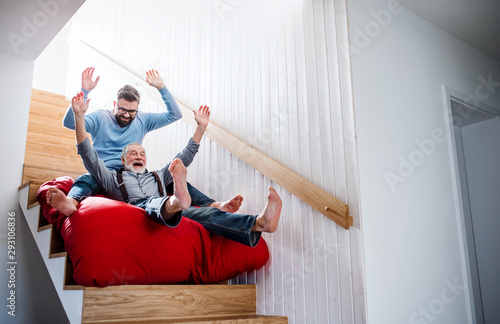 An adult hipster son and senior father indoors at home, having fun Poster Mural XXL