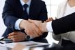 Business people shaking hands after contract signing at the glass desk in modern office. Unknown businessman, male entrepreneur with colleagues at meeting or negotiation. Teamwork, partnership and