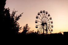Silhouette Of A Ferris Wheel At Sunrise (sunset) Of The Sun On A Background Of Trees And Grass.