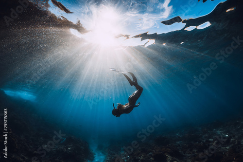 Woman freediver with fins underwater Fototapeta