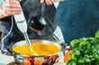 Chefkoch mit stabmixer kocht leckere kürbissuppe