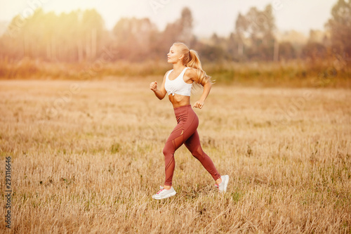 Athletic young blonde girl is jogging in park dawn, concept running for health