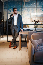 Handsome Businessman In Suit Standing And Talking On Smartphone In Modern Office.