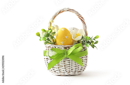 Photo colorful easter eggs and spring flowers in basket isolated on white background