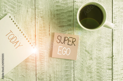 Obraz Conceptual hand writing showing Super Ego. Concept meaning The I or self of any demonstrating that is empowering his whole soul Stationary placed next to a coffee cup above wooden table - fototapety do salonu