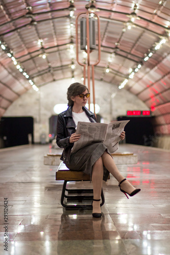 Obraz Business woman sitting reading a newspaper. Beautiful girl in a business suit and sunscreen sitting reading a newspaper at the subway station. A woman in a jacket. Success concept - fototapety do salonu