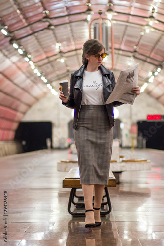 Business woman with a cup of coffee is reading a newspaper Wallpaper Mural