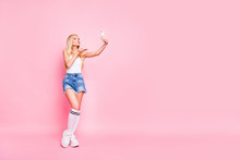 Full Length Photo Of Coquette Blogger Make Self Portrait Send Air Kisses With Her Cell Phone Wear Stylish Modern Outfit Tank-top Denim Jeans Shorts White Sneakers Isolated Over Pastel Color Background