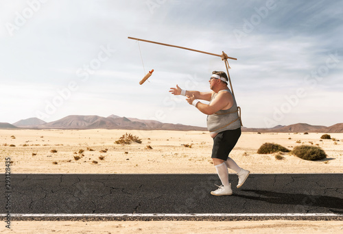 Fototapeta Funny overweight man chasing the hot dog on the stick through the empty road with copy space obraz
