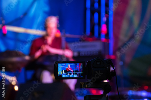 Video camera recording ethnic open air concert. Man with tank drum or hang on blurry abstract bokeh background - 293131292