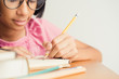 Asian little girl wears glasses while sit writing on desk at her home