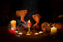 Witch Guessing On Wax On The Altar In The Dark. Female Hands With Sharp Black Nails Making Passes Above Candles, Pumpkin, Nuts, Magic Herbs, Dry Leaves, Selected Focus, Low Key