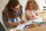 Mother helps her daughter with homework assignment .