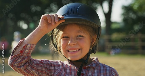 Slika na platnu Authentic shot of a little girl with a  helmet smiling in the camera at riding stable on a sunny day