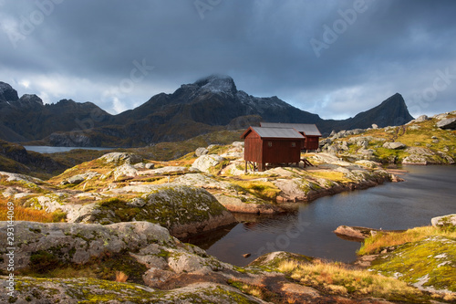 Lofoten Islands Norway. Mountain autumn landscape. Hike to Mount Munkan, wooden houses, a shelter and a lake in the sunlight against a stormy sky