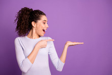 Photo Of Charming Lady Holding New Sale Product On Open Arm Indicate Finger On Low Prices Advising To Buy Wear Casual Pullover Isolated Purple Color Background