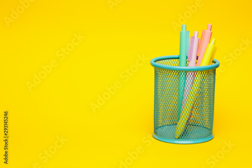 Fotografie, Obraz  Blue pencil basket holder with colored pens on vivid yellow background with negative space