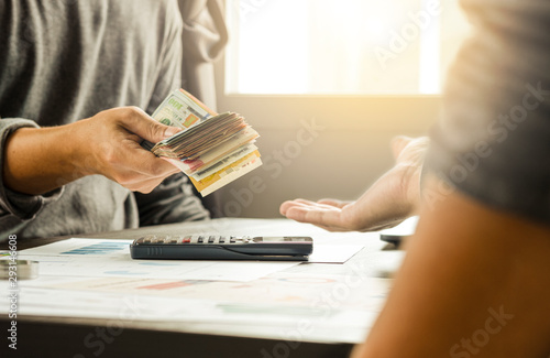 Fotografía  Two businessmen give and take US dollar banknote